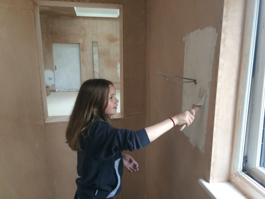 A female scout painting the newly plastered walls