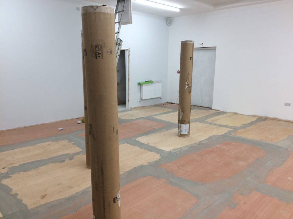 Rolls of lino stand like columns on top of a prepared floor.