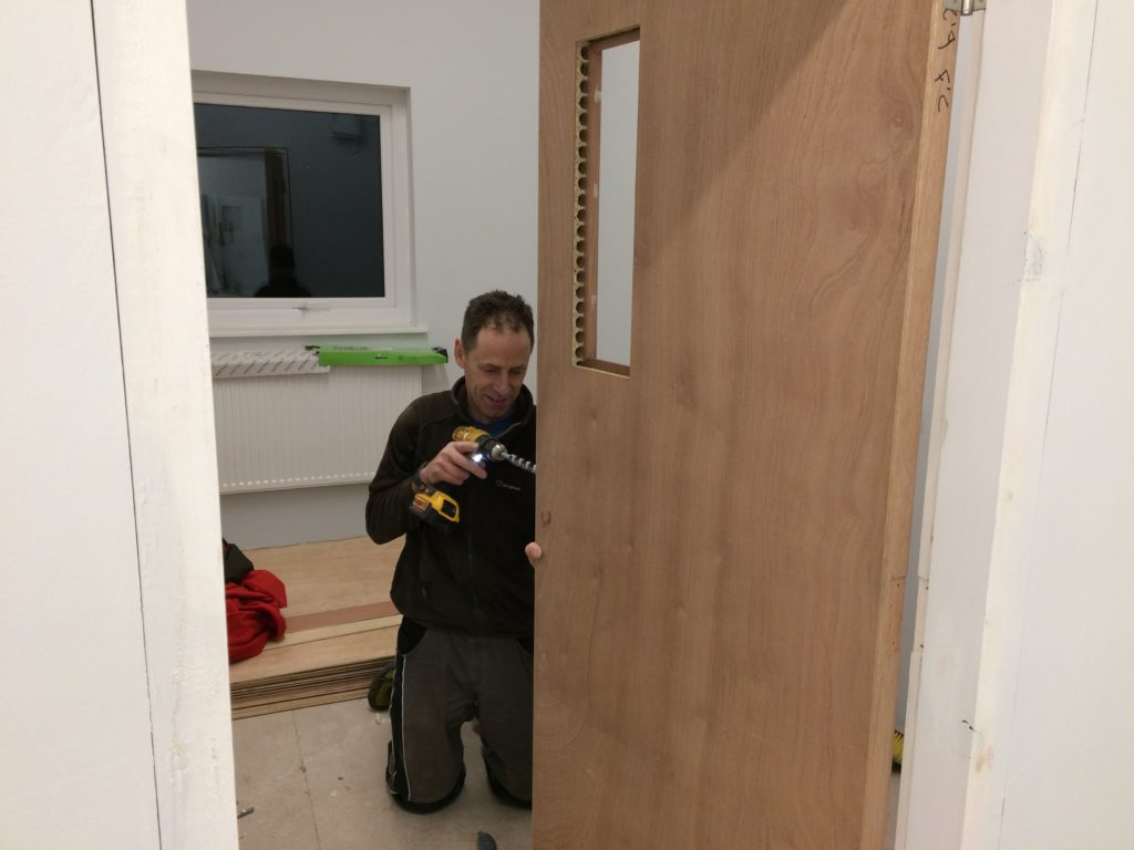 A parent (who happens to be a carpenter by trade) fitting the door locks.