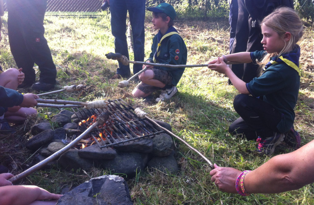 Cubs cooking bread twists over a camp fire