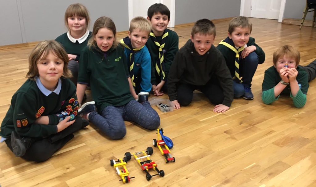 Cubs sitting in front of their lego racing cars