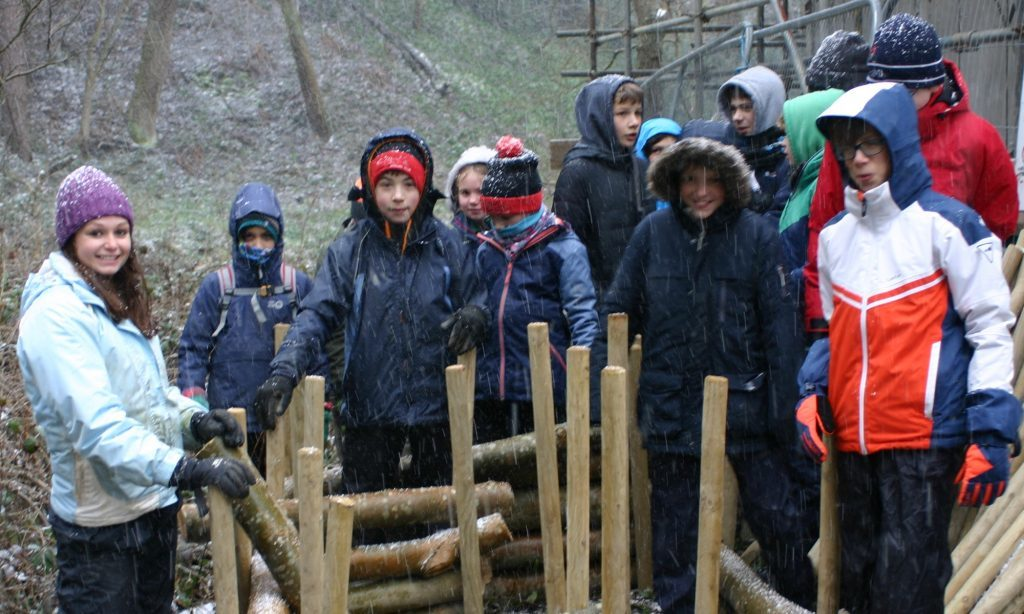 A group of scouts well-wrapped up against the elements standing next to some wooden stakes they are hammering into the ground.