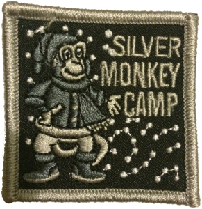 The badge is made of silver stitching on a black background. It shows a monkey dressed up in winter clothes, standing in the snow. Beside it are the words SILVER MONKEY CAMP.