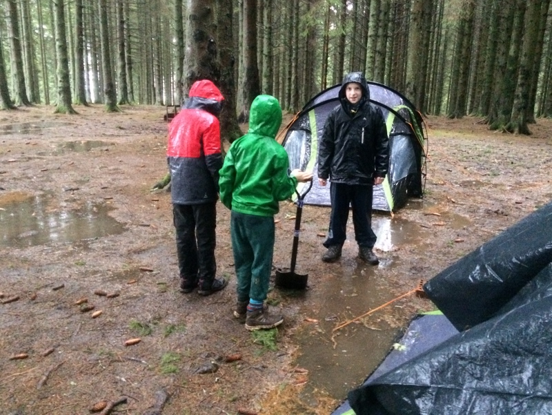 Scouts in waterproofs, digging trenches around their tents,