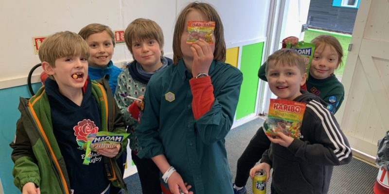 Cubs holding packs of sweets